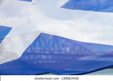 Forth Rail Bridge, Edinburgh taken with a fluttering Saltire flag veiling the bridge.  Image taken from a boat on the Firth of Forth.