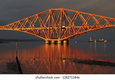 Forth Rail Bridge at sunset with dark grey sky
