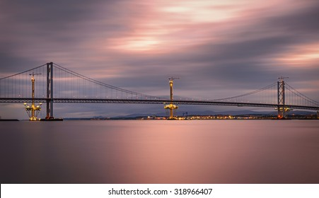 Forth Road Bridge and the Queensferry Crossing under construction in Edinburgh, Scotland, United Kingdom. Long exposure.