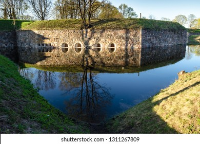 Fortification wall with tree on it, shooting windows and shadows reflecting in flooded defensive moat. Daugavpils, Latvia.