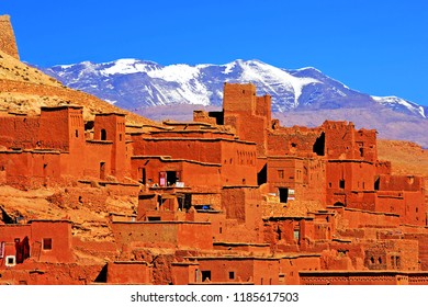 Fortified city of Aït Benhaddou (Ait Ben-Haddou) with the High Atlas mountains covered by snow in blue sky, Morocco