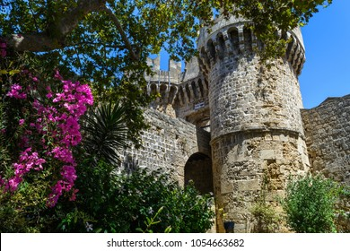 Fortified entrance into the medieval castle of the Grand Masters Palace in Rodos, Island of Rhodes, Greece surrounded by green trees and pink flowers, blue sky