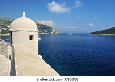 The fortified walls of the historical and UNESCO listed city of Dubrovnik, Croatia with luxury cruisers anchored in the bay