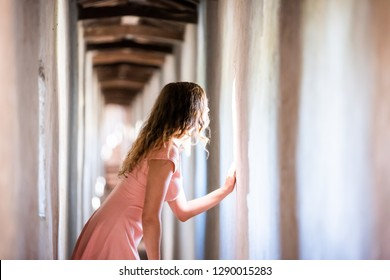 Fortress tunnel path passage in Castiglione del Lago in Italy during summer with woman looking out of window in historic town village fort