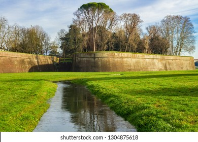 The fortress wall of Lucca (Tuscany, Italy). Green grass and narrow moat surrounding the fortress wall.