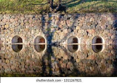 Fortress wall with shooting windows and shadows reflecting in flooded defensive moat. Daugavpils, Latvia.