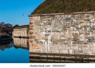 Fortress walls and moat with grass-covered roof at Fort Monroe National Monument in Hampton Virginia.