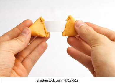 Fortune cookie being pulled apart with a blank fortune against a white background