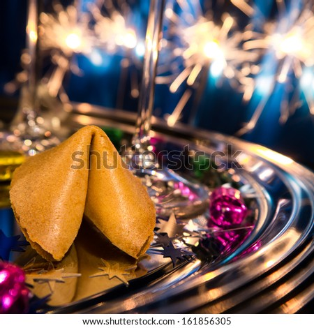 fortune cookie and champagne glass on tray on new year's eve