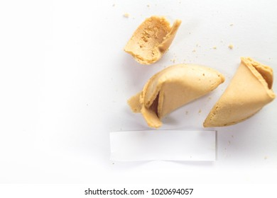 Fortune cookie isolated on white, cracked with message paper