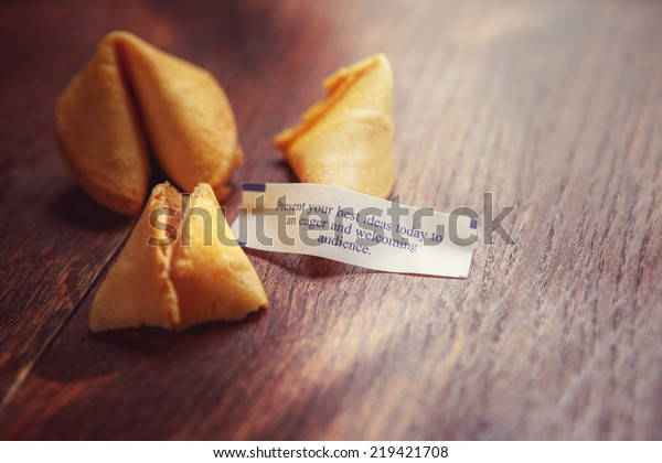 """Fortune cookie with fortune """"Present your best ideas today to an eager and welcoming audience"""".  Shallow focus."""