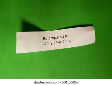 "Fortune cookie fortune reading  ""Be prepare to modify your plan"" on green background."