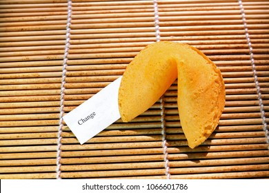 Fortune cookie with fortune showing the word change,  tanbamboo  mat background.