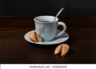 Fortune cookies and exclusive Chinese blue tea in a light blue cup on a wooden surface on a black background. It can be used for food and cooking magazines; healthy lifestyle books; for print