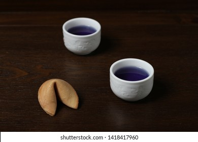 Fortune cookies and two Chinese porcelain tea bowls on a wooden surface against a black background. It can be used for food and cooking magazines; healthy lifestyle books; for interior, print design
