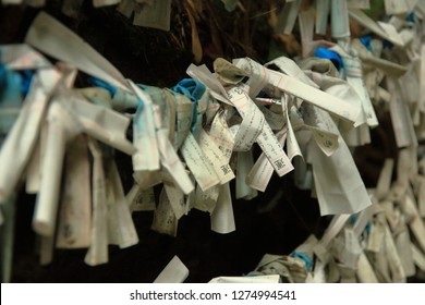 Fortune paper was tied at a pole for a bad fortune from Japanese fortune telling strip, Omikuji