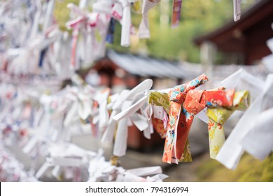 Fortune paper was tied  at a pole for a bad fortune from Japanese fortune telling strip, Omikuji.