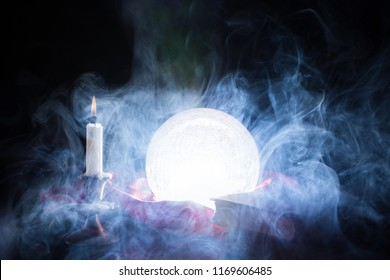 Fortune teller crystal ball smokes and lights on table with candle in candlestick and books. Halloween concept. Close up, selective focus