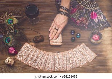 Fortune teller female hand and tarot cards on wooden table. Fortune teller divination.