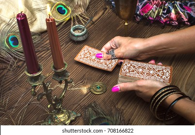 Fortune teller female hands and tarot cards on wooden table. Concept of divination.