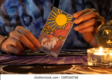 Fortune teller of hands holding THE SUN card and tarot cards on table near burning candles in candle light.Tarot cards spread on table with crystal ball.Forecasting concept.