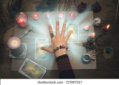 Fortune teller reading future with tarot cards on wooden table.