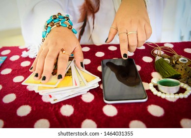 Fortune teller reading fortune lines on screen smartphone modern horoscopes online fortune telling application Palmistry Psychic readings and clairvoyance hands concept with Tarot cards divination