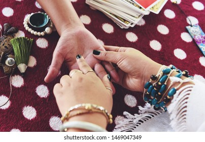 Fortune teller reading fortune lines on hand Palmistry Psychic readings and clairvoyance hands concept with Tarot cards divination
