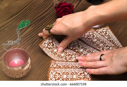 Fortune teller  removes card from  tarot cards deck on wooden table. Divination concept.