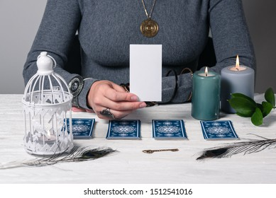 Fortune teller showing a blank tarot card in hand with a copy space for image.