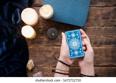 Fortune teller with tarot cards in the hand on brown table background.