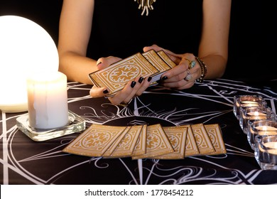 Fortune teller or tarot reader of hands shuffling cards.Tarot cards face down on a table near a crystal ball and burning candles.Mystic and darkness background.Forecasting concept.
