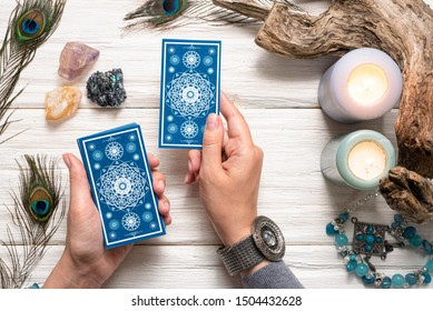 Fortune teller woman and a blue tarot cards over white wooden table background.