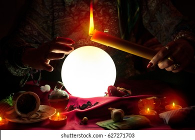Fortune teller woman holding candle above glowing crystal ball