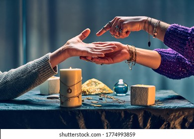 Fortune teller woman reading palm lines around candles and other magical accessories. Witch during fortune telling, palmistry and divination. Magic ritual