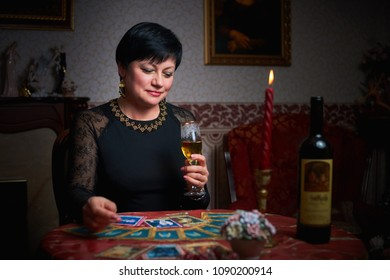 Fortune teller woman reading tarot cards in the dark room with a glass of wine