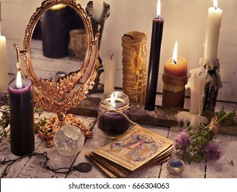 Fortune telling still life with the tarot cards, mirror and burning candles. Halloween concept. Mystic background with occult and magic objects on witch table.