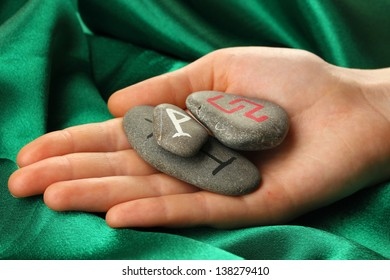 Fortune telling  with symbols on stone in hand on green fabric background