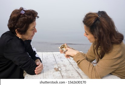 Fortune telling and traditional turkish coffee concept on coast. Woman telling fortune to elder woman by inspecting the brown grounds remaining in coffee cup. Young woman guessing on coffee grounds.