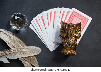 fortune-telling cards with magic owl, birds' feathers and crystal on black velvet background