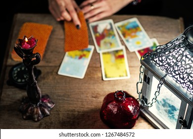 Fortune-telling on traditional tarot cards on the old wooden table with a lantern and a candle. Selective focus.