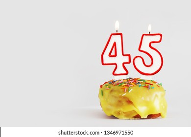Forty five years anniversary. Birthday cupcake with white burning candles with red border in the form of number Forty five. Light gray background with copy space