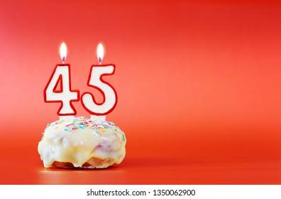Forty five years birthday. Cupcake with white burning candle in the form of number 45. Vivid red background with copy space
