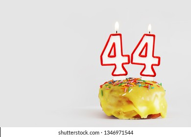 Forty four years anniversary. Birthday cupcake with white burning candles with red border in the form of number Forty four. Light gray background with copy space