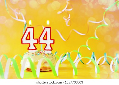 Forty four years birthday. Cupcake with burning candles in the form of number 44. Bright yellow background with copy space