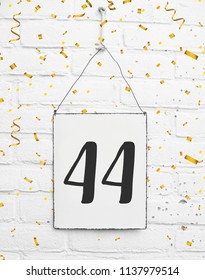 forty four years old birthday congratulations text with golden confetti sign white brick background