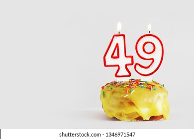 Forty nine years anniversary. Birthday cupcake with white burning candles with red border in the form of number Forty nine. Light gray background with copy space