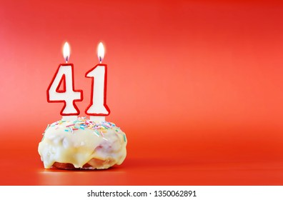 Forty one years birthday. Cupcake with white burning candle in the form of number 41. Vivid red background with copy space