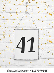 forty one years old birthday congratulations text with golden confetti sign white brick background