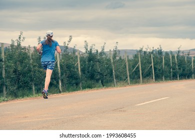 forty something trail runner running along a dirt road